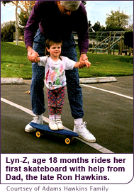 Lyn-Z, age 18 months rides her first skateboard with help from Dad, the late Ron Hawkins.