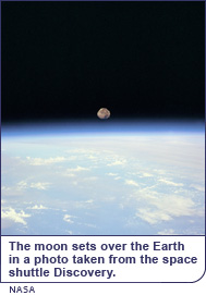 The moon sets over the Earth in a photo taken from the space shuttle Discovery.